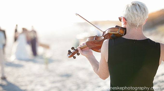 Rearview of Maura playing violin at a Wilmington beach wedding