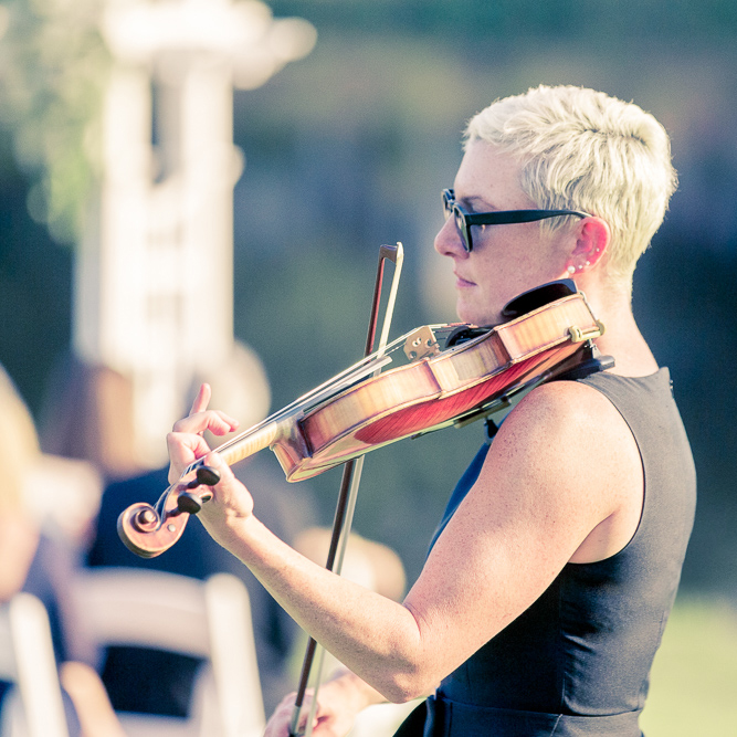 Side view of Maura and her violin at an outdoor wedding in Wrightsville Beach