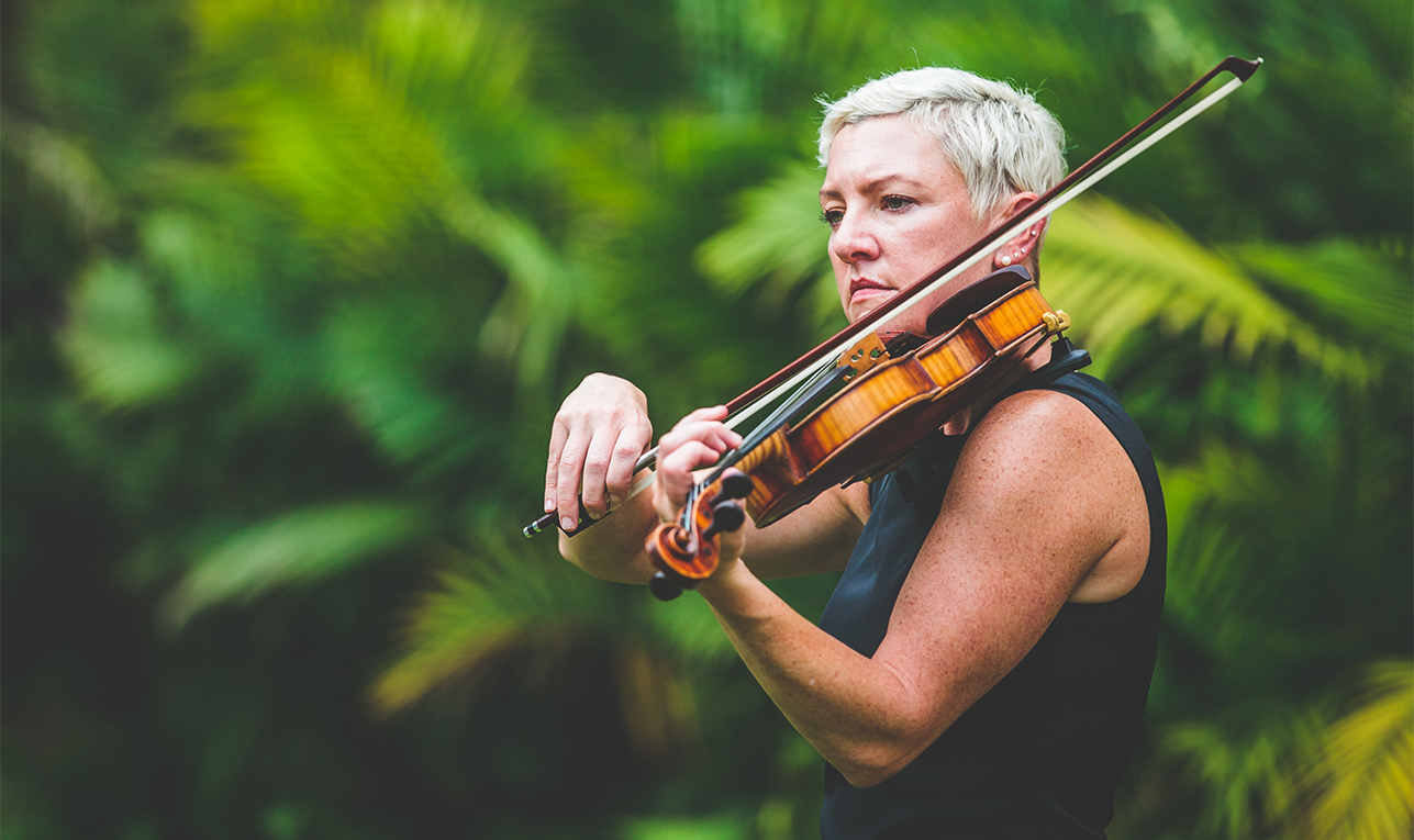 Close up of Maura playing the violin in front of palm trees